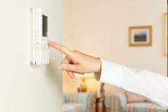 Kaukasische Dame, die modernen Thermostat bedrängt Lizenzfreie Stockbilder