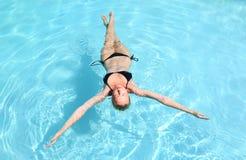 Kaukasische dame die in zwembad drijven Stock Afbeeldingen