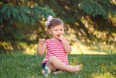 Kaukasische de peuterzitting van het babymeisje in park buiten stock foto's