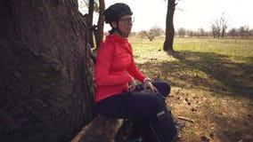 Kaukasische de vrouwensport van de sportfietser van het park van de wegfiets dichtbij boom vrouwenatleet in sportkleren en helm e stock video