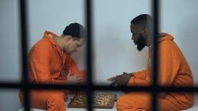 Kaukasische en Afro-Amerikaanse gevangenismedebewoners die schaak in cel, hobby in gevangenis spelen stock footage