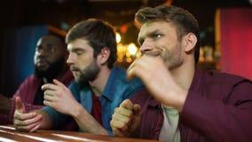Kaukasische en zwarte mannelijke vrienden die voetbal op spel in bar letten, team het verliezen stock footage