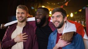 Kaukasische en zwarte mannelijke vrienden die volkslied zingen, golvend Engelse vlag stock footage