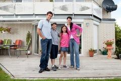 Kaukasische Familie, die vor Haus steht Lizenzfreies Stockfoto