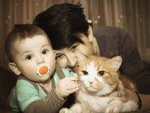 Kaukasische Familienmutter und -baby, die mit Katze spielt Stockfotos