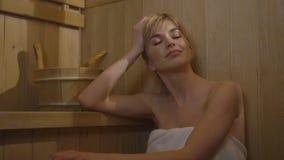 Kaukasische Frau der Junge recht, die in der Sauna sich entspannt Stockfotografie