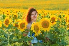 Kaukasische Frau der Junge recht im Sonnenblumenfeld Lizenzfreie Stockfotografie