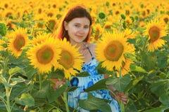 Kaukasische Frau der Junge recht im Sonnenblumenfeld Stockfoto