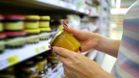 Kaukasische Frau der Nahaufnahme übergibt nahe den Shopregalen, die hellen Honig im Lebensmittelgeschäftmarkt wählen stock footage