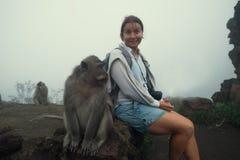 Kaukasische Frau, die in den kurzen Hosen sitzen nahe Affen ist Stockbild