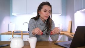 Kaukasische Frau, die in der Küche frühstückt und einen Laptop verwendet stock video footage