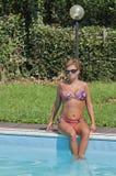 Kaukasische Frau, die am Rand des Schwimmens Pools des im Freien sitzt Stockfotos