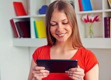 Frau, die Tablette-PC und -c$lächeln betrachtet Stockfotos