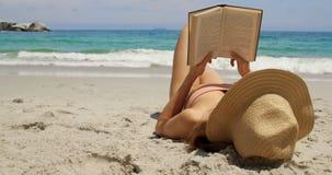 Kaukasische Frau im Hut ein Buch auf dem Strand 4k lesend stock video