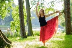 Kaukasische Frau im roten Rock, der Balancenyoga asana im Sommerpark tut stockfoto