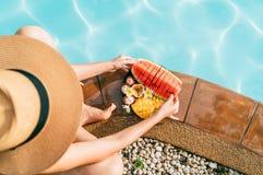 Kaukasische Frau im Strohhut, der auf Swimmingpoolseite nahe Platte der Kamera der tropischen Früchte sitzt und versucht, Wasserm lizenzfreie stockfotografie