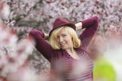 Kaukasische Frau mit nahem blühendem Baum des langen blonden Haares und des purpurroten Fedorahutes, Arme hinter ihrem Kopf mit d stockbild