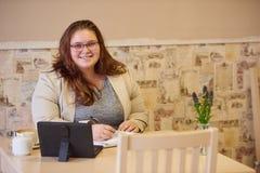 Kaukasische Geschäftsfrau der Plusgröße, die an der Kamera in der Kaffeestube lächelt lizenzfreie stockfotografie