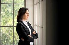Kaukasische Geschäftsfrau des Vertrauens kreuzte ihre Arme und das Fenster heraus schauen Stockfotografie