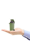 Kaukasische Hand, die einen grünen Abfalleimer hält Lizenzfreies Stockbild