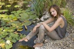 Kaukasische het meisjeszitting van Gingerish bij de oever van het meer. Stock Afbeeldingen