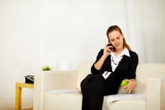 Kaukasische jonge bedrijfsvrouw die aan bank werkt Stock Foto's