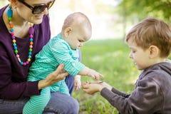 Kaukasische jonge de babydochter van de vrouwenholding terwijl kleuterschool die insecten op zijn hand tonen stock foto's
