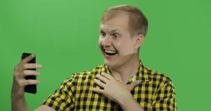 Kaukasische jonge mens in geel overhemd die mobiele telefoon voor videogesprek met behulp van stock afbeelding