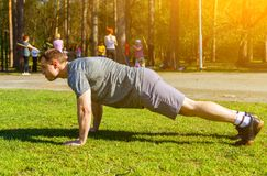 Kaukasische jonge sportman die oefeningsplank op uitgestrekte wapens doen of opdrukoefeningen uitvoeren royalty-vrije stock foto
