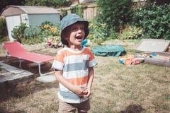 Kaukasische jongen die gestripte t-shirt en hoed met grappige gezichtsuitdrukking buiten dragen op huisbinnenplaats op de zomerda royalty-vrije stock foto's