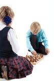 Kaukasische jongen die met in hand schaakcijfer denken terwijl het spelen van spel met meisje, geïsoleerde witte achtergrond Stock Foto