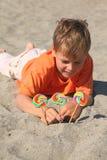 Kaukasische jongen die op strand, lollys in zand ligt stock afbeeldingen