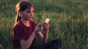 Kaukasische jongen met de telefoon op de aard Jongenstiener met een smartphone bij zonsondergang Jongen met de zonsondergang van  stock footage