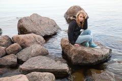 Kaukasische Jugendliche, die auf Küstensteinen sitzt Lizenzfreie Stockfotografie