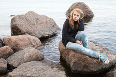 Kaukasische Jugendliche, die auf Küstensteinen sitzt Stockfotos