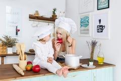 Kaukasische junge blonde Mutter und kleine schöne Tochter in den weißen Kochkappen essen Früchte auf Küche Stockbild