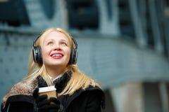 Kaukasische junge Frau in den großen Kopfhörern hörend Musik Lizenzfreie Stockfotos