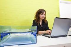 Kaukasische junge Frau, die an ihrer Laptop-Computer an ihrem Schreibtisch arbeitet Lizenzfreie Stockfotografie