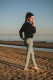 Kaukasische junge Frau im schwarzen Sweatshirt, Blue Jeans allein gehend auf Strand im Sonnenuntergang Porträt im Freien nachdenk Stockfotografie