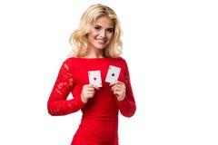 Kaukasische junge Frau mit dem langen hellen blonden Haar in der Abendausstattung, die Spielkarten hält Getrennt schürhaken Stockbilder