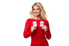 Kaukasische junge Frau mit dem langen hellen blonden Haar in der Abendausstattung, die Spielkarten hält Getrennt schürhaken Stockbild
