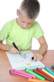 Kaukasische Jungenzeichnung auf Papier mit Zeichenstiften Lizenzfreie Stockfotos