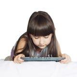Kaukasische Kinderkindermädchenschwester, die auf dem Bett mit dem Tabletten-PC lokalisiert liegt Stockfoto