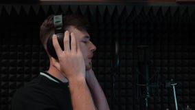Kaukasische knappe jongen die emotioneel lied zingen De aantrekkelijke mens registreert stem in professionele muziekstudio De jon stock video
