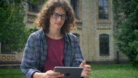 Kaukasische knappe mens in glazen met krullend haar gebruikend tablet en bekijkend camera, die in park dichtbij universiteit zitt stock footage