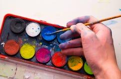 Kaukasische männliche Künstlerhand unter Verwendung des blauen Aquarells von der Palette Lizenzfreie Stockfotografie