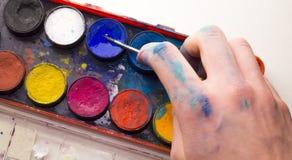 Kaukasische männliche Künstlerhand unter Verwendung des blauen Aquarells von der Palette Stockbild