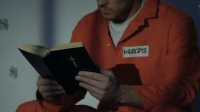 Kaukasische mannelijke gevangene die heilige bijbel in cel, hoop voor vergiffenis, geloof lezen stock video