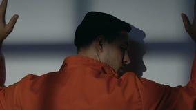 Kaukasische mannelijke gevangene die met handen op muur op straf van wacht wachten stock video