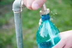 Kaukasische mannelijke hand die een plastic fles vullen Royalty-vrije Stock Afbeeldingen